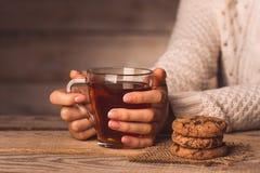 Copo do chá preto nas mãos de uma menina e de cookies na tabela imagens de stock