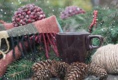 Copo do chá quente em uma tabela de madeira rústica Ainda a vida dos cones, guita, patskthread, abeto ramifica Neve tirada Imagem de Stock
