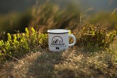 Copo do chá quente no fundo da natureza durante o por do sol r Acampamento de verão imagens de stock royalty free