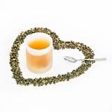 Copo do chá verde, folhas de chá verdes na forma do coração e prata Fotografia de Stock
