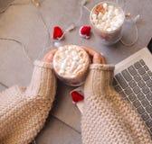 Copo do chocolate quente com marshmallow em uma mão da mulher foto de stock