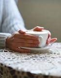 Copo do cofee nas mãos fêmeas no close up da tabela fotografia de stock