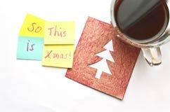 Copo do coffe em um cartão de Natal e de notas pegajosas sobre um fundo branco Fotos de Stock Royalty Free