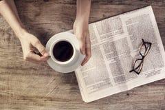 Copo do jornal da leitura da jovem mulher e de café da terra arrendada fotografia de stock
