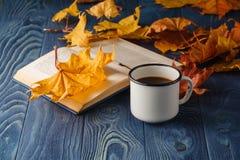 Copo do livro velho da sagacidade do chá e das folhas de outono na tabela de madeira Fotografia de Stock Royalty Free