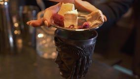 Copo do metal com a bebida na barra Mulher posta sobre o sauser do metal da bacia com partes de queijo, de rosas secas e de framb video estoque