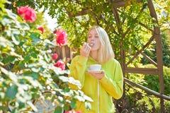 Copo do prazer Aprecie o cappuccino cremoso delicioso no jardim de floresc?ncia Cappuccino gourmet da bebida da menina A mulher a fotos de stock royalty free