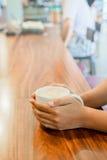 Copo do punho da mão das mulheres do café quente na tabela de madeira Fotografia de Stock
