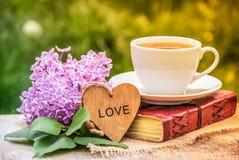 Copo do ramo lilás e do livro do chá O tempo de mola… aumentou as folhas, fundo natural Chá e livro no jardim fotografia de stock royalty free