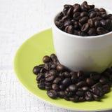 Copo dos feijões de café na tabela Imagens de Stock