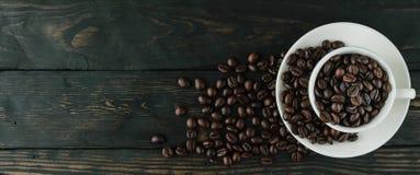 Copo dos feijões de café na vista superior de madeira preta Imagens de Stock