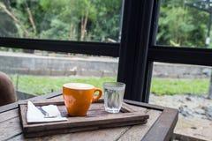 Copo e água potável de café na tabela Fotografia de Stock Royalty Free