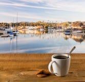 Caneca de café na tabela de madeira pelo porto fotografia de stock royalty free