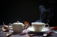 Copo e bule quentes de chá no fundo de madeira com vapor, fotografia de stock royalty free