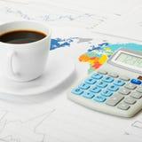 Copo e calculadora de café sobre o mapa do mundo e alguma carta financeira - ascendente próximo Imagens de Stock Royalty Free