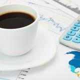 Copo e calculadora de café sobre o mapa do mundo e alguma carta financeira - ascendente próximo Foto de Stock Royalty Free