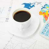 Copo e calculadora de café sobre o mapa do mundo e alguma carta financeira - ascendente próximo Fotografia de Stock Royalty Free