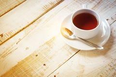 Copo e colher de chá em pires com a tabela da luz solar da manhã para o espaço da cópia Imagens de Stock