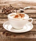 Copo e feijões de café na tabela da madeira do vintage Fotografia de Stock