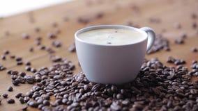 Copo e feijões de café na tabela de madeira vídeos de arquivo