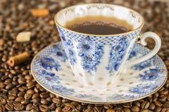 Copo e feijões de café no fundo de madeira bonito, tom azul da tabela da cor do vintage Fotos de Stock