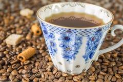 Copo e feijões de café no fundo de madeira bonito, tom azul da tabela da cor do vintage Fotografia de Stock Royalty Free