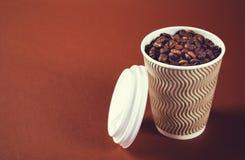 Copo e feij?es de papel de caf? no fundo marrom fotografia de stock royalty free