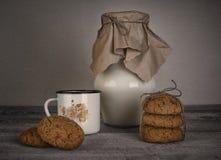 Copo e frasco do leite e de cookies caseiros Foto de Stock Royalty Free