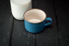 Copo e garrafa do leite na tabela de madeira retro Imagens de Stock