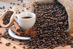Copo e grões de café na tabela de madeira Foto de Stock