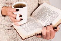 Copo e livro de chá nas mãos das jovens mulheres com pregos e a camiseta pretos fotografia de stock