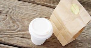 Copo e pacote descartáveis de café na prancha de madeira filme