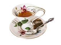 Copo e pires de chá antigos de China com saquinho de chá e a colher de prata fotos de stock
