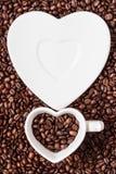 Copo e pires no fundo dos feijões de café Foto de Stock Royalty Free