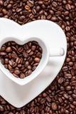 Copo e pires no fundo dos feijões de café Fotos de Stock