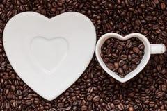Copo e pires no fundo dos feijões de café imagens de stock royalty free