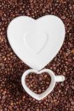 Copo e pires no fundo dos feijões de café Foto de Stock
