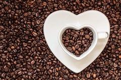 Copo e pires no fundo dos feijões de café Fotografia de Stock Royalty Free