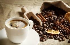 Copo e saco completamente dos feijões de café, laranjas secadas no linho Fotografia de Stock