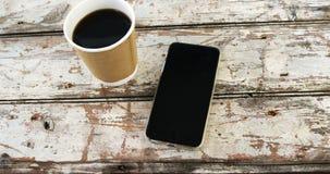 Copo e telefone celular descartáveis de café na prancha de madeira vídeos de arquivo