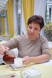 Copo envelhecido médio elegante da terra arrendada da mulher do chá Imagens de Stock