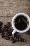 Copo, feijões de café no fundo da opinião superior do close up da placa de madeira Fotos de Stock