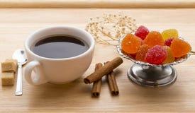 Copo fresco do chá quente, do doce de fruta colorido, dos cubos do bastão de açúcar mascavado e das varas de canela Imagem de Stock Royalty Free