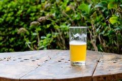 Copo meio cheio da cerveja sobre a tabela de madeira Imagem de Stock