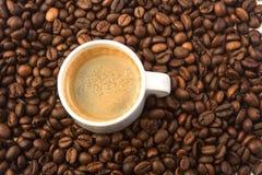 Copo pequeno branco e muitos feijões de café Fotografia de Stock