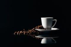 Copo pequeno do café preto em um fundo escuro com feijões de café fotografia de stock