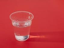 Copo plástico da água fresca sobre o vermelho, sidelit Imagens de Stock Royalty Free