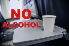 Copo plástico na tabela no plano durante o voo consumo do álcool a bordo ilustração royalty free