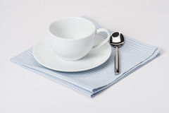 Copo, placa e colher no algodão dobrado do guingão Imagem de Stock
