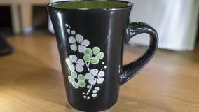 Copo preto bonito com as flores brancas e verdes Fotos de Stock